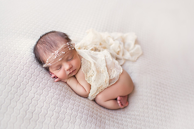 newborn with pearl headband on cream backdrop